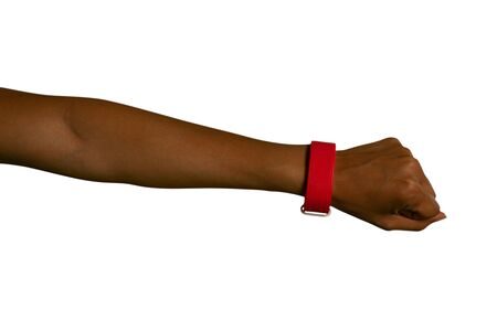 Close up of the outstretched arm of a young mixed race woman with fist clenched, wearing a red wristband