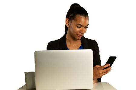 Front view close up of a young mixed race woman using a laptop and looking at her smartphone