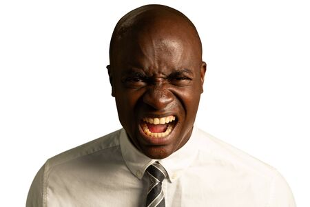 Portrait close up of a bald young African American businessman wearing a shirt and tie, looking straight to camera screaming
