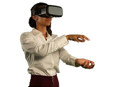 Vista lateral de cerca de una joven mujer de raza mixta con una camisa blanca y un casco de realidad virtual, mirando hacia adelante con las manos extendidas frente a ella una encima de la otra, como si sostuviera o tocara Foto de archivo