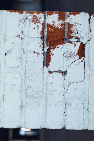 Close up detail of the interior of an abandoned warehouse space showing a white brick wall