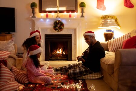 Side view of a mixed race couple sitting on the floor with their young daughter in their sitting room at Christmas, wearing santa hats, smiling, the man is playing guitar