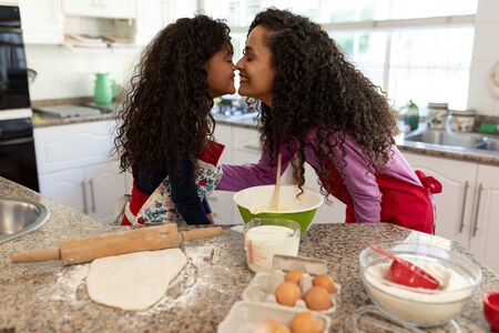 Side view of a mixed race woman in a kitchen with her young daughter at Christmas, making cookies, facing each other and touching noses