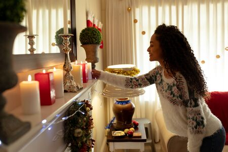 Side view of a mixed race woman in her sitting room at Christmas, smiling and arranging candles on a mantlepiece