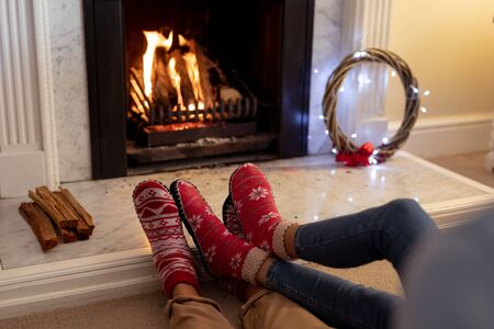 Legs of a mixed race couple in their sitting room at Christmas, lying on the floor by a fireplace