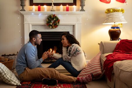 Side view of a mixed race couple in their sitting room at Christmas, facing each other holding hands