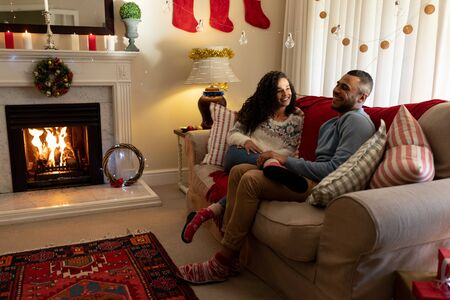 Side view of a mixed race couple in their sitting room at Christmas, sitting on a sofa talking and smiling