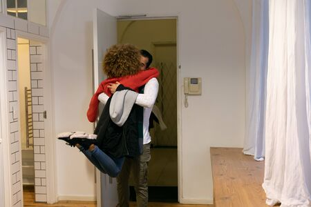 Back view of a young mixed race woman and man embracing in the hallway at the open front door of an apartment Reklamní fotografie