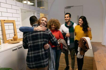 Vue de face d'un groupe de jeunes amis multiethniques masculins et féminins adultes arrivant à une fête debout dans le couloir d'un appartement, une femme portant un plat de nourriture pour la fête
