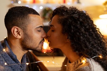 Side view close up of a mixed race couple in their sitting room at Christmas, facing each other with eyes closed Фото со стока