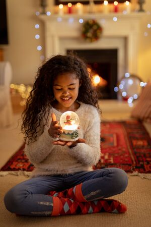 Front view of a young mixed race girl in her sitting room at Christmas, smiling and holding a snow globe