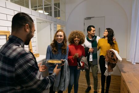 Front view of a group of young adult multi-ethnic male and female friends arriving at a party standing in the hallway of an apartment, one woman carrying a dish of food for the party