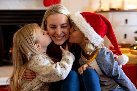 Front view close up of a young Caucasian woman sitting on the floor between her young son and daughter in their sitting room at Christmas time, the children kissing her on either cheek Reklamní fotografie