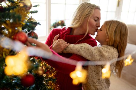 Front view of a young Caucasian woman kissing her young daughter beside the Christmas tree in their sitting room, with Christmas star decorations hanging in the foreground Reklamní fotografie - 130553178