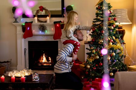 Side view of a middle aged Caucasian man with his young daughter sitting on his shoulders decorating the Christmas tree in their sitting room, with Christmas star decorations hanging in the foreground Stock Photo