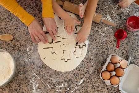 Overhead view of the hands of young Caucasian mother and her son and daughter in their kitchen at Christmas time making cookies, cutting out shapes in dough with cookie cutters on a kitchen worktop