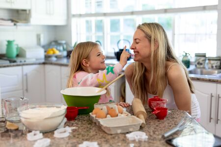 Side view of a happy young Caucasian woman with her young daughter in their kitchen at Christmas time making cookies and smiling as her daughter touches her nose with flour on her finger Banco de Imagens