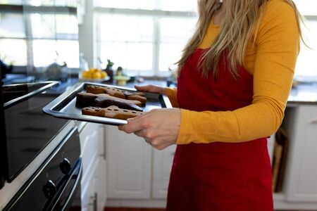 Side view mid section of a young Caucasian woman in her kitchen at Christmas time standing in front of the oven wearing an apron holding a baking tray with gingerbread man cookies on it
