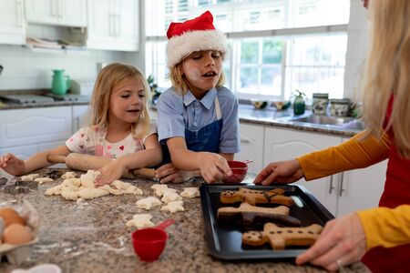 Front view of a young Caucasian mother with her young daughter and son in their kitchen at Christmas time making cookies together, mum holding a baking tray with cooked gingerbread man cookies on it, her son wearing a Santa hat