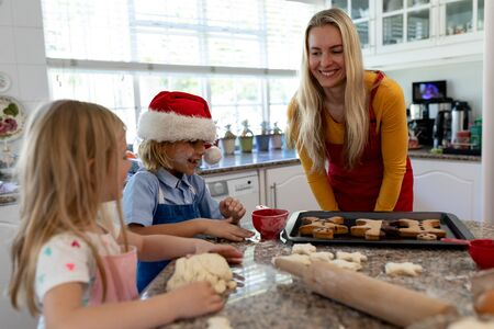 Front view of a happy young Caucasian mother with her young daughter and son in their kitchen at Christmas time making cookies, the children rolling dough, and a baking tray with cooked gingerbread man cookies on it on the worktop Banco de Imagens
