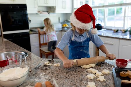 Front view of young Caucasian boy rolling dough on a worktop with his sister in the background in their kitchen at Christmas time while making cookies