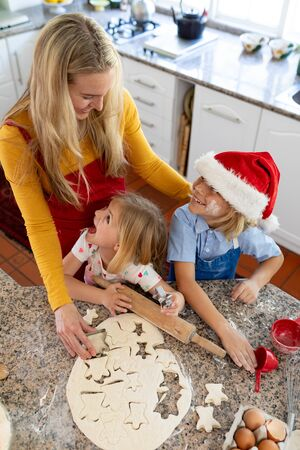 Front view of a happy young Caucasian mother with her young daughter and son in their kitchen at Christmas time making cookies and smiling, the boy wearing a Santa hat Banco de Imagens