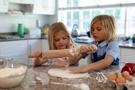 Front view of young Caucasian brother and sister in their kitchen at Christmas time making cookies, rolling dough with a rolling pin together Banco de Imagens