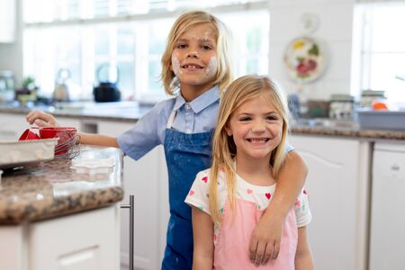 Front view of happy young Caucasian brother and sister in their kitchen at Christmas time smiling with flour on their faces while making cookies at Christmas time Banco de Imagens