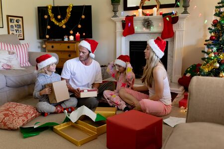 Side view of a caucasian family sitting on the floor with their young son and daughter in their sitting room at christmas time, wearing santa hats and opening presents