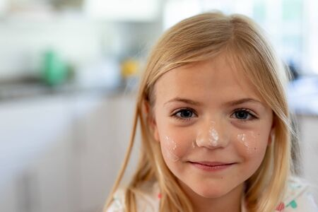 Portrait of a happy young blonde haired Caucasian girl smiling to camera with flour on her face while making cookies at Christmas time in her kitchen