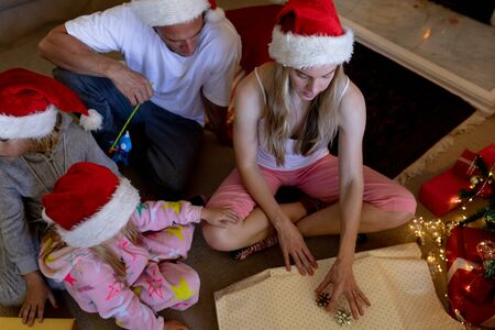 High angle view of a caucasian family sitting on the floor with their young son and daughter in their sitting room at christmas time wearing santa hats, opening presents