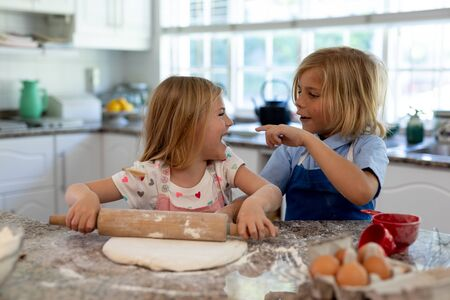 Front view of young Caucasian brother and sister in their kitchen at Christmas time making cookies, rolling dough, looking at each other and smiling