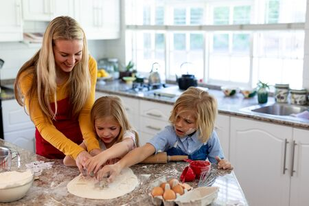 Front view of a happy young Caucasian mother with her young daughter and son in their kitchen at Christmas time making cookies, having fun using cookie cutters to cut shapes in rolled dough