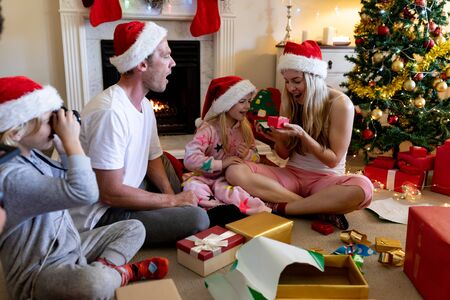 Side view of a caucasian family sitting on the floor with their young son and daughter in their sitting room at christmas time wearing santa hats, opening presents and smiling