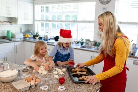 Side view of a happy young Caucasian mother with her young daughter and son in their kitchen at Christmas time making cookies, mum holding a baking tray with cooked gingerbread man cookies on it, her son wearing a Santa hat Banco de Imagens