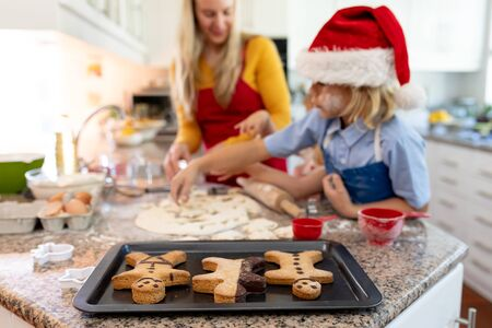 Front view of a happy young Caucasian mother with her young daughter and son in their kitchen at Christmas time making cookies, with a baking tray with cooked gingerbread man cookies on it on the worktop in the foreground, her son wearing a Santa hat Banco de Imagens