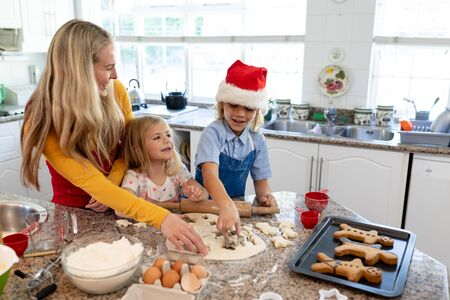 Front view of a happy young Caucasian mother with her young daughter and son in their kitchen at Christmas time making cookies, cutting shapes from dough, with cooked gingerbread man cookies in a baking tray on the worktop