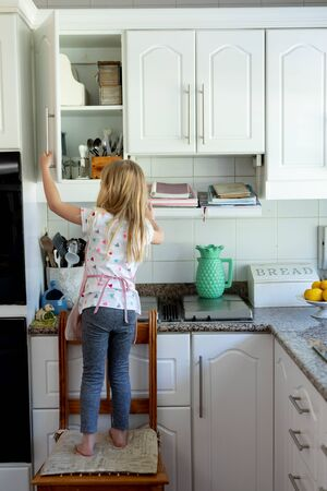 Rear view of a young Caucasian girl in her kitchen standing on a chair and looking in a kitchen cabinet