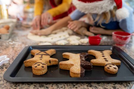 Front view close up of a young Caucasian mother with her young daughter and son in their kitchen at Christmas time making cookies, with a baking tray with cooked gingerbread man cookies on it on the worktop in the foreground