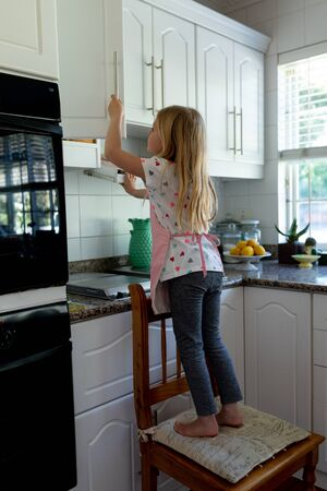 Side view of a young Caucasian girl in her kitchen standing on a chair and looking in a kitchen cabinet