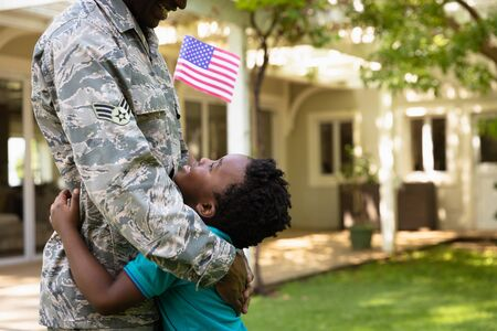Side view close up of a young adult African American male soldier in the garden outside his home, embracing his young son, who is looking up at him smiling and holding a US flag, thier house in the background