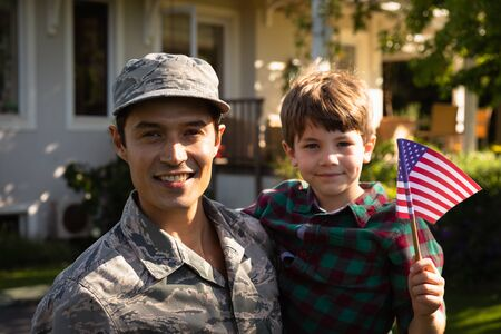 Portrait of a young adult mixed race male soldier  carrying his son who is holding a US flag