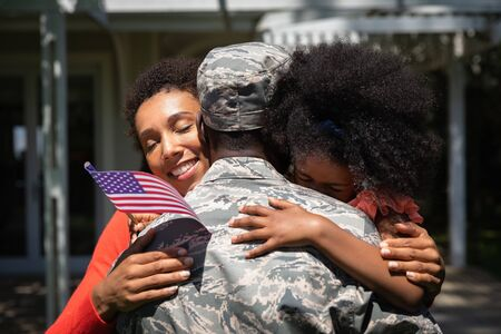 Rear view close up of a young adult African American soldier embracing his young daughter and his mixed race wife Banque d'images