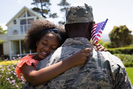 Rear view close up of a young adult African American male soldier in the garden carrying his daughter