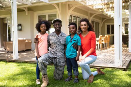 Soldier kneeling with his arms around his young son and daughter, his mixed race wife beside them