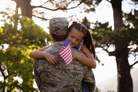 Soldier hugging his daughter holding a US flag