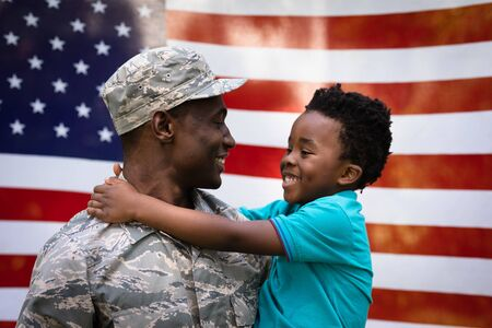 Side view close up of a young adult African American male soldier carrying his young son