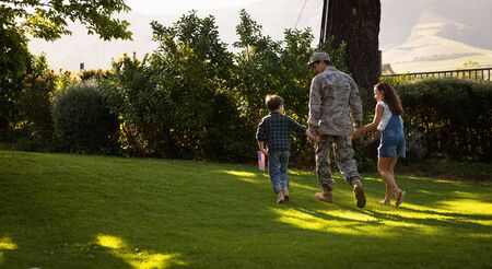 Rear view of a young adult mixed race male soldier in the garden outside his home, holding hands and walking with his young son and daughter, his son holding a US flag