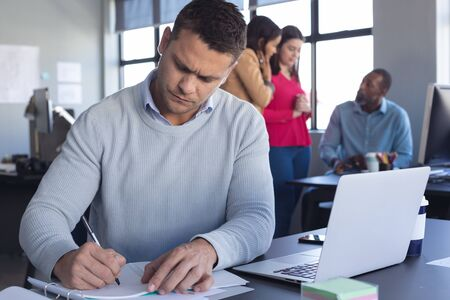 Front view close up of a Caucasian male business creative working in a casual modern office, writing notes with a pen and paper and using a laptop computer, with colleagues working in the background
