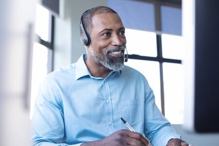 Vista frontale ravvicinata di un business creativo maschio afroamericano che lavora in un ufficio moderno casual, prendendo appunti, sorridendo e parlando su un auricolare del telefono Archivio Fotografico